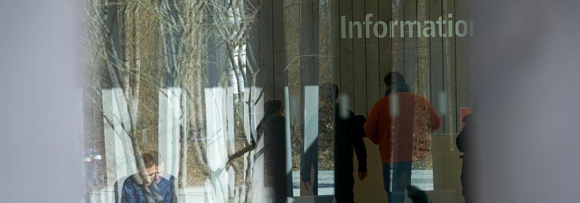 Foto der Fassade des Besucherzentrums, durch die sich ein Besucher vor der Infotheke spiegelt