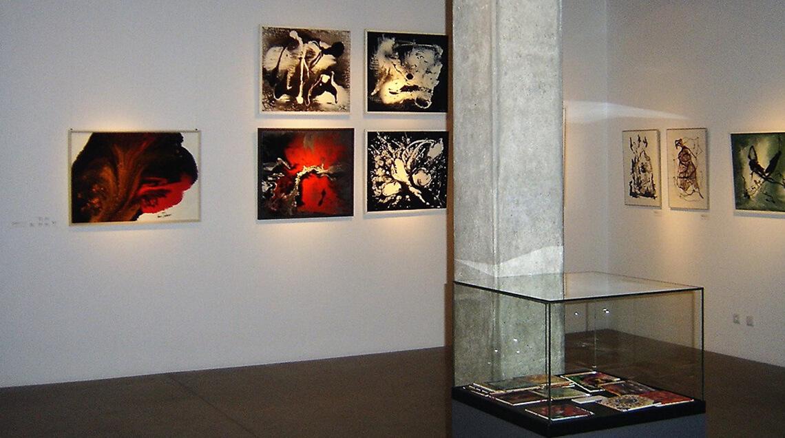 """Der Blick in die Ausstellung """"Ich male nur für mich"""" zeigt einige Gemälde an einer Wand im Hintergrund, im Vordergrund ist eine Betonsäule und eine Vitrine mit kleineren Gemälden zu sehen."""