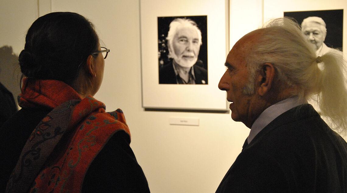Mehrere Besucher betrachten die schwarz-weiße Fotografie eines Überlebenden