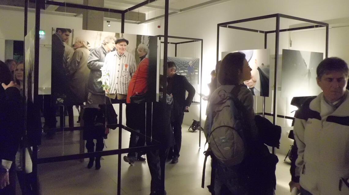 """Besucher in der Doppelausstellung """"Generationen"""" und """"Blickwinkel"""" betrachten Fotografien. Mehrere würfelförmige Metallhalterungen stehen im Raum verteilt, an diesen sind Bilder befestigt, die ehemalige Häftlinge zeigen, die an die Orte ihres Leidens zurückkehren."""