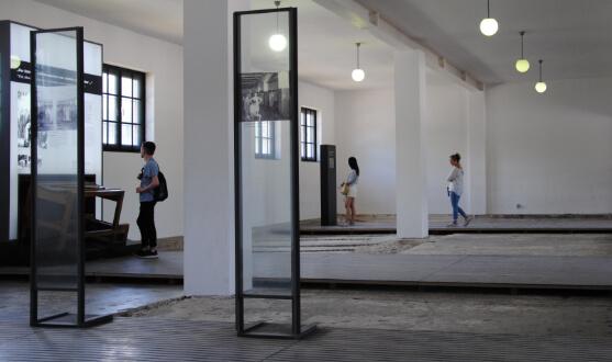 Großer weiß gestrichener Raum, in der Mitte durch Säulenbögen unterteilt. Der Betonboden ist uneben.