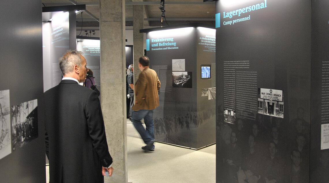 """Mehrere Besucher laufen durch die Ausstellung """"Sie gaben uns wieder Hoffnung"""". Es sind einige graue Schautafeln aufgestellt, an denen Texte und Bilder zu sehen sind."""