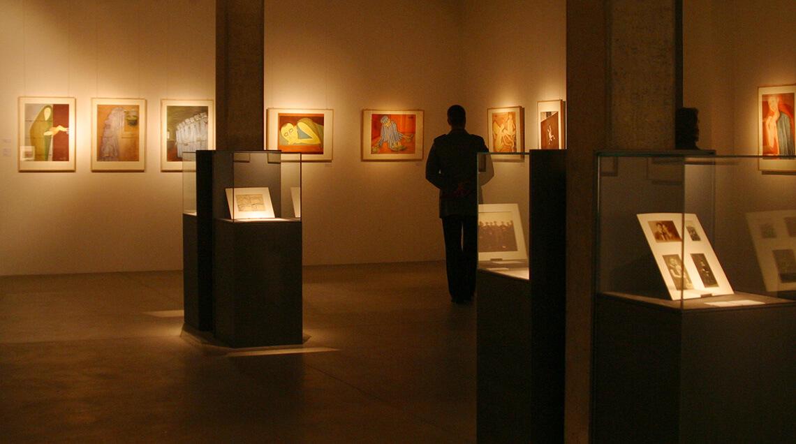 """Blick in die Ausstellung """"Egon Marc Lövith – ich zeige wenig und sage alles"""". Ein Mensch im Hintergrund betrachtet einige an der Wand hängende Gemälde in einem schwach beleuchteten Raum."""