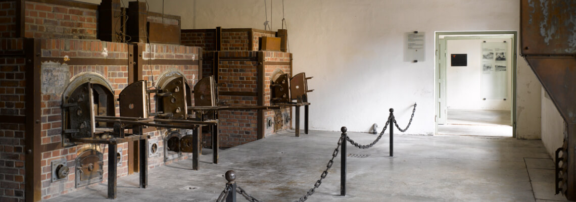 Blick auf drei Verbrennungsöfen, den Dachstuhl des Krematoriums und eine Ausstellungstafel im folgenden Raum