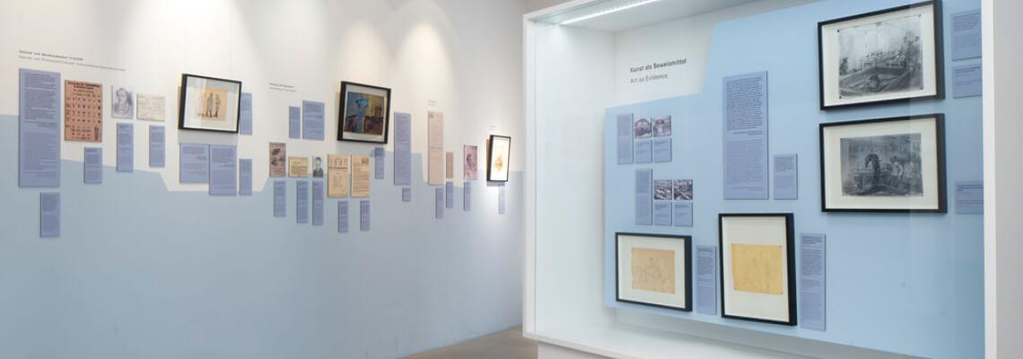 מבט על ויטרינת תצוגה וקיר עם תמונות וציורים של ניצול דכאו גאורג טאובר