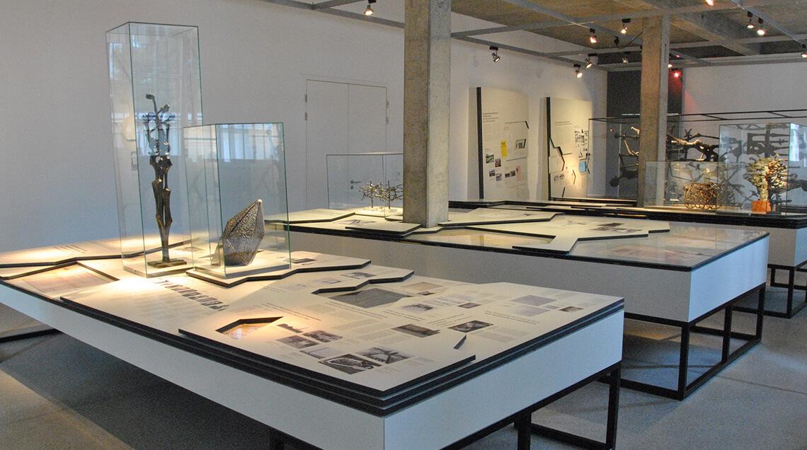 Blick auf die Ausstellungstische mit Detailzeichnungen und Modellen des Mahnmals
