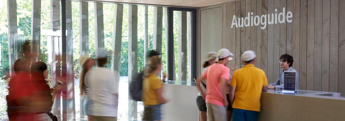Besucherinnen und Besucher vor der Theke des Audioguide-Verleihs im Besucherzentrum der KZ-Gedenkstätte Dachau