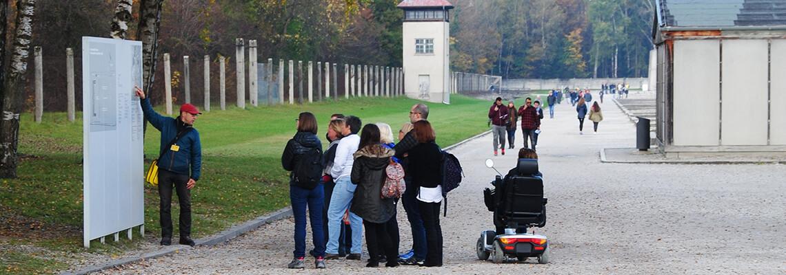 Besucherinnen und Besucher bei einem geführten Rundgang. Einer der Besucher ist im Rollstuhl unterwegs.
