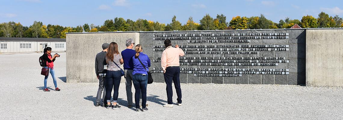 Wenige erwachsene Besucherinnen und Besucher vor einem Relief des Internationalen Mahnmals auf dem ehemaligen Appellplatz