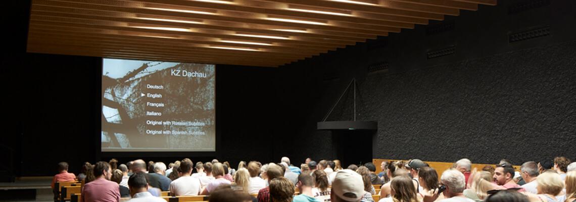 מבקרים באולם הקולנוע של אתר ההנצחה של מחנה הריכוז דכאו