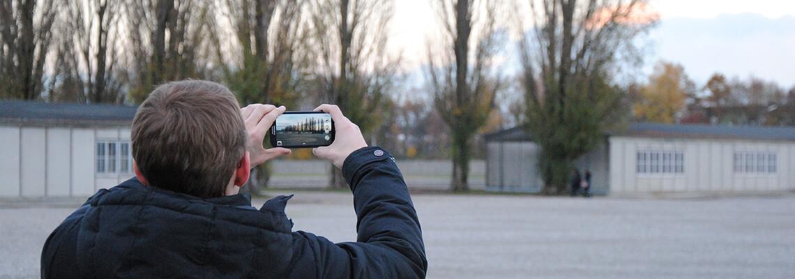 Junger Besucher, der mit seinem Smartphone die ehemalige Lagerstraße fotografiert.