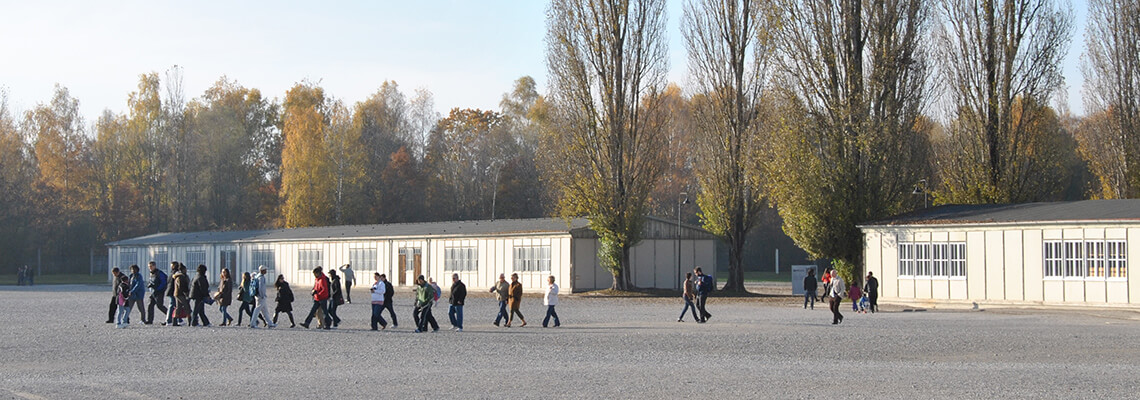 Besucherinnen und Besucher bei einem geführten Rundgang vor einer der rekonstruierten Modellbaracken