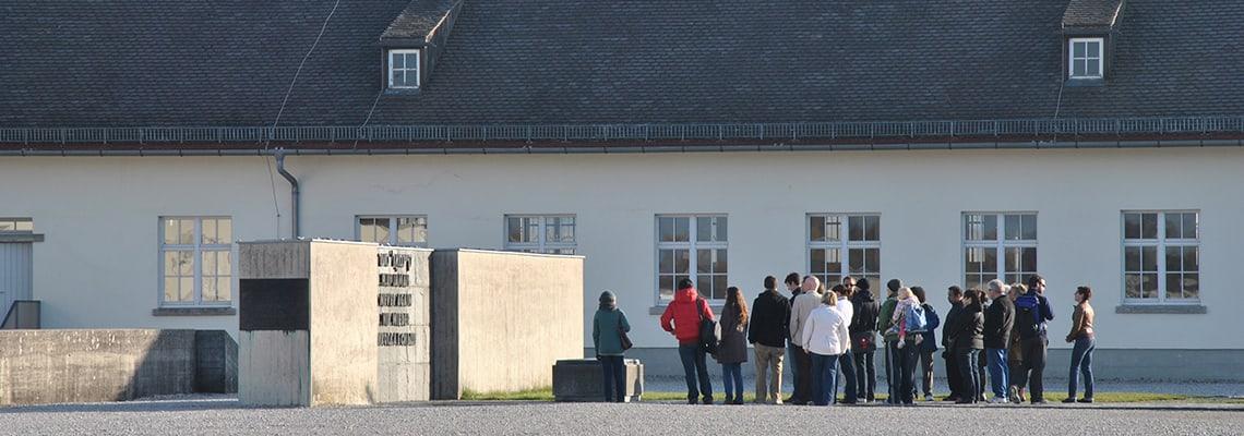 Ein Besuchergruppe steht am Internationalen Mahnmal vor dem ehemaligen Wirtschaftsgebäude.