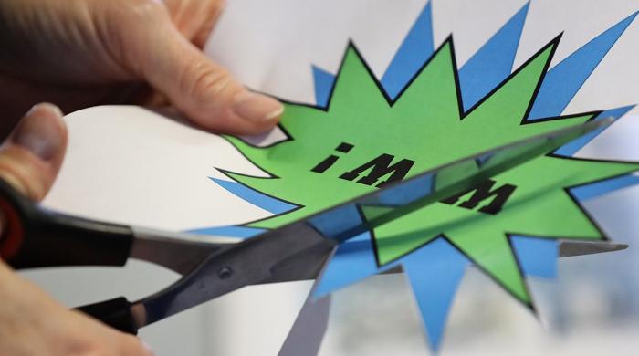 Eine Teilnehmerin schneidet mit einer Schere eine typische Comic-Sprechblase aus