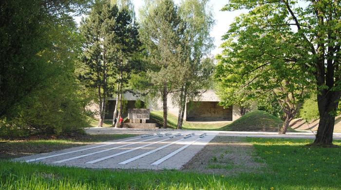 """Zwei Besucher stehen vor dem Mahnmal auf dem ehemaligen """"SS-Schießplatz Hebertshausen"""", rechts von ihnen ist der Kugelfang aus Beton zu sehen."""