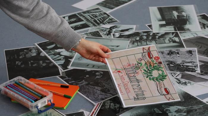 Auf dem Boden liegen verschiedene Bilder. Eine Teilnehmerin hebt eines auf und hält es hoch.