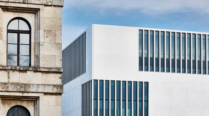 """Einem Fassadendetail des NS-Dokumentationszentrums München steht auf dem Foto die Teilansicht des benachbarten ehemaligen """"Führerbaus"""" gegenüber."""