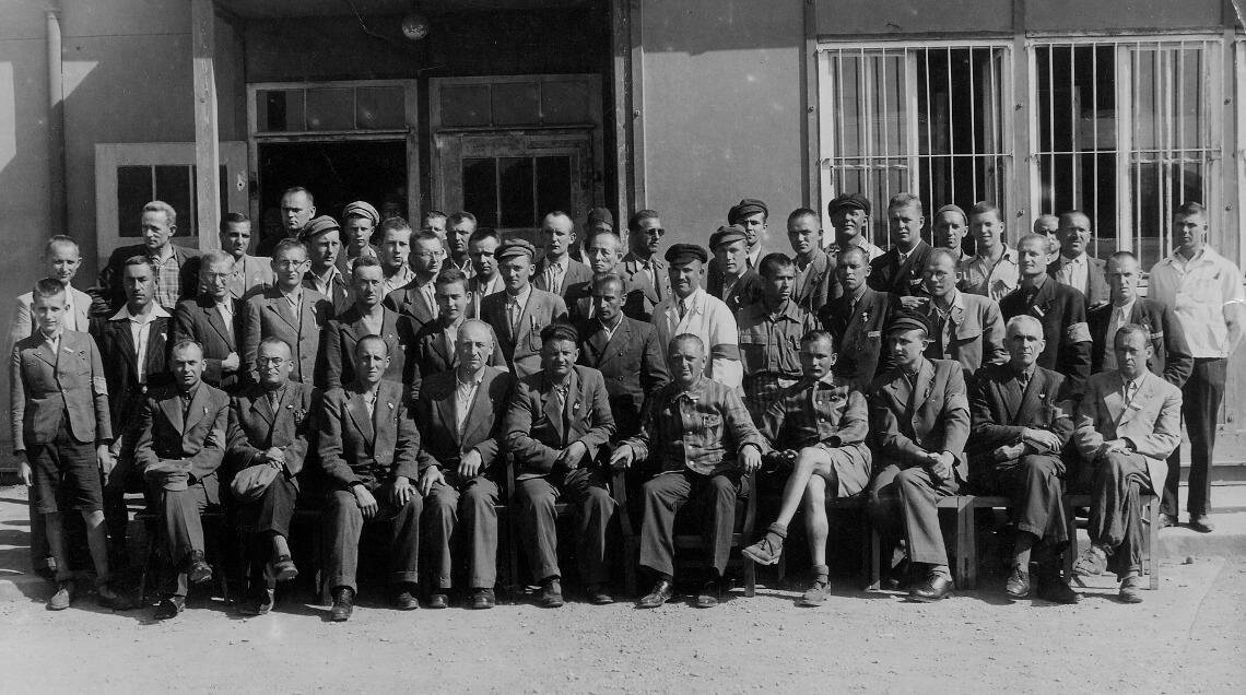 Eine Gruppe befreiter polnischer Häftlinge vor einer Baracke, vermutlich im Mai 1945