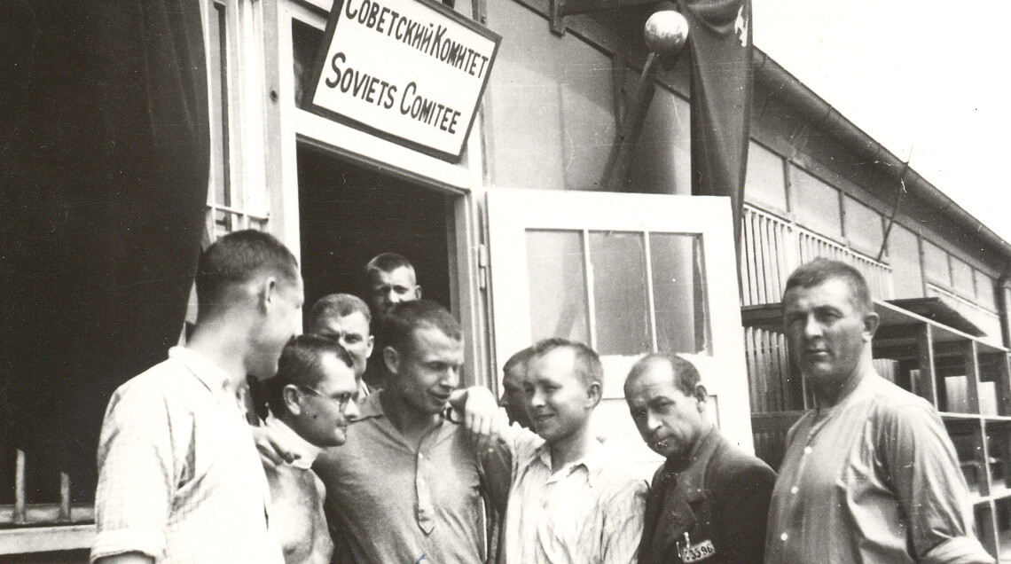 Befreite Häftline vor einer Baracke mit der Aufschrift des Sowjetischen Häftlingskomitees vermutlich im Mai 1945