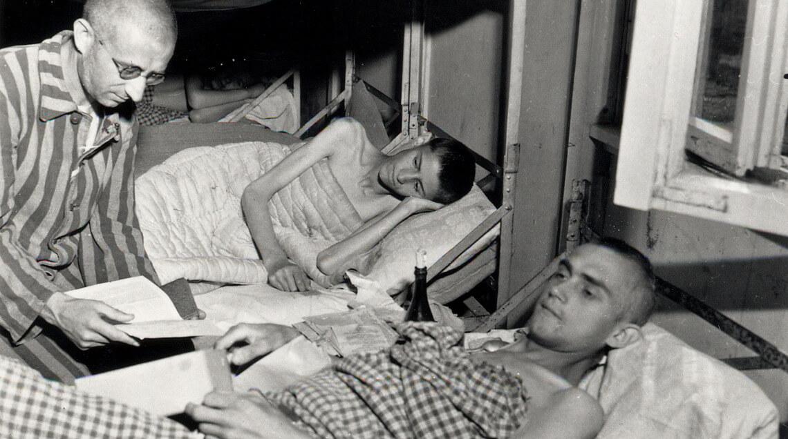 Überlebende des KZ Dachau in einem Schlafraum kurz nach der Befreiung durch die US-Armee (Mai 1945)