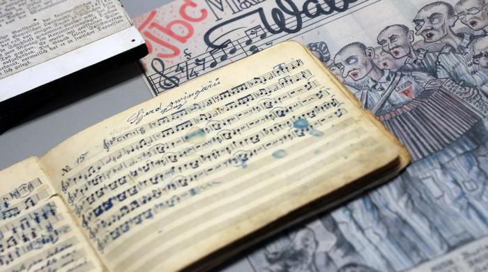 Abgebildet sind Werke, die heimlich im KZ Dachau entstanden sind: ein mit Kompositionen gefülltes Notenheft und eine gezeichnete Einladung zu einem Konzert