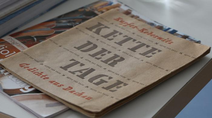 """Arbeitstisch mit verschiedenen Büchern und Heften. Obenauf liegt das Heft """"Kette der Tage"""" mit den Gedichten von Edgar Kupfer-Koberwitz, der das KZ Dachau überlebte"""