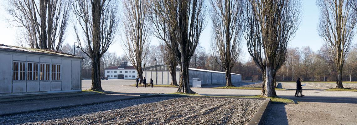 Blick von der ehemaligen Lagerstraße über die beiden Modellbaracken zum ehemaligen Jourhaus