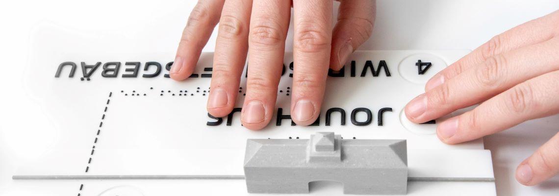 Finger ertasten ein taktiles Modell mit dem Jourhaus und Brailleschrift.