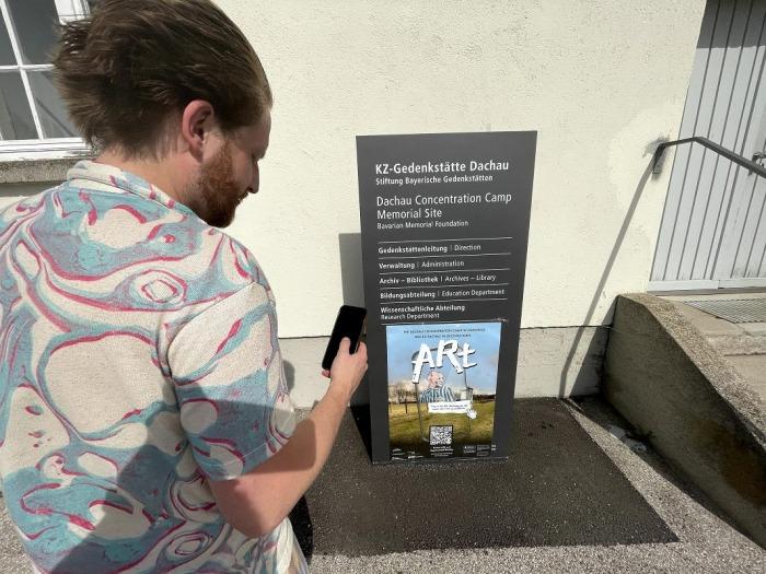 Ein Mann scannt das ARt Poster in der KZ-Gedenkstätte