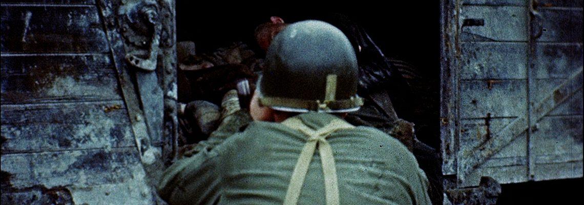 Ein Kameramann des U.S. Army Signal Corps in Dachau, Mai 1945. Aus: [World War II color footage], George Stevens, [Liberation at Dachau] (2. bis 7. Mai 1945). Library of Congress.